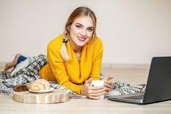 La ragazza beve il tè e legge da un computer portatile Il concetto di vita Fotografia Stock Libera da Diritti