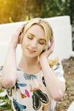 La ragazza bianca millenaria ascolta musica sulle cuffie mentre sorride all'aperto alla luce calda fotografia stock