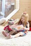 La ragazza bionda abbastanza piccola si siede vicino al giocattolo molle su tappeto Fotografia Stock Libera da Diritti
