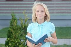 La ragazza bionda adorabile con il libro in mani si avvicina alla scuola La scolara gradisce imparare e leggere fotografia stock libera da diritti