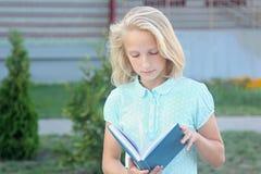 La ragazza bionda adorabile con il libro in mani si avvicina alla scuola La scolara gradisce imparare e leggere fotografia stock