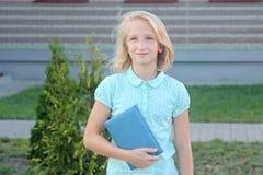 La ragazza bionda adorabile con il libro in mani si avvicina alla scuola La scolara gradisce imparare e leggere immagine stock