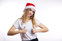 La ragazza bionda affascinante felice in cappello e maglietta rossi di Santa mostra il segno del pollice su ed i sorrisi alla mac fotografie stock