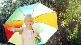 La ragazza bionda allegra gode della pioggia 5 anni Nascondendosi sotto un ombrello stock footage