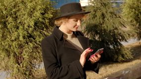 La ragazza bionda attraente in cappello nero del cappotto prende il telefono dallo zaino moderno che si siede dalle piante sul mo stock footage