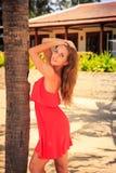 la ragazza bionda in capelli rossi di tocchi esamina la macchina fotografica contro la villa Fotografia Stock