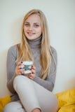 La ragazza bionda che beve il suo caffè, mangia i biscotti ed ha letto un libro Immagine Stock Libera da Diritti