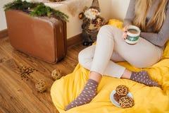 La ragazza bionda che beve il suo caffè, mangia i biscotti ed ha letto un libro Fotografie Stock Libere da Diritti