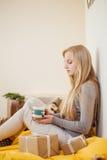 La ragazza bionda che beve il suo caffè, mangia i biscotti ed ha letto un libro Immagini Stock Libere da Diritti