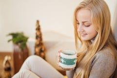 La ragazza bionda che beve il suo caffè, mangia i biscotti ed ha letto un libro Immagini Stock