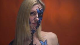 La ragazza bionda con bodypainting sul suo fronte esamina il suo amico e gira la sua testa stock footage