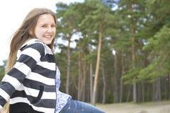 La ragazza bionda con capelli lunghi sta sedendosi e sorridendo immagine stock libera da diritti