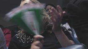La ragazza bionda con un fan negli applausi delle mani, si rallegra per il gruppo HD, 1920x1080 Movimento lento video d archivio