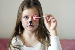 La ragazza bionda con un trucco che imita un gatto tiene in sua mano i chups di un chupa immagini stock libere da diritti