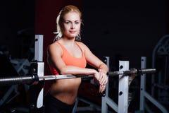 La ragazza bionda di forma fisica con l'ente perfetto di forma riposa dopo l'allenamento di sport in palestra che si appoggia il  Fotografie Stock Libere da Diritti
