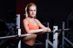 La ragazza bionda di forma fisica con l'ente perfetto di forma riposa dopo l'allenamento di sport in palestra che si appoggia il  Fotografia Stock Libera da Diritti
