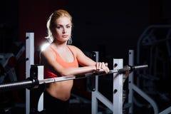La ragazza bionda di forma fisica con l'ente perfetto di forma riposa dopo l'allenamento di sport in palestra che si appoggia il  Fotografia Stock