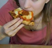 La ragazza bionda divertente in maglietta rosa mangia la ragazza bionda pizzaFunny in maglietta rosa mangia la pizza fotografia stock libera da diritti