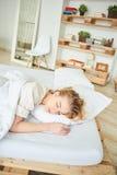La ragazza bionda dorme su un letto Fotografia Stock Libera da Diritti