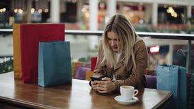 La ragazza bionda felice lavora con uno smartphone alla tavola in caffè con i sacchetti della spesa su  video d archivio