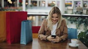 La ragazza bionda felice lavora con uno smartphone alla tavola in caffè con i sacchetti della spesa su  stock footage