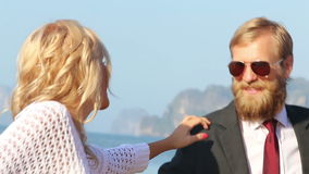 la ragazza bionda ferma il chitarrista con la mano ed abbraccia il collo sulla spiaggia stock footage