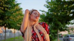 La ragazza bionda graziosa del ritratto raddrizza i suoi capelli lunghi e condizione sorridente sveglia sul vicolo con gli alberi archivi video