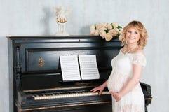 La ragazza bionda incinta gioca il piano Fotografia Stock