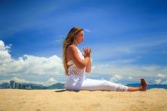 la ragazza bionda negli occhi chiusi del pizzo si siede in asana di yoga Immagine Stock
