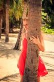 la ragazza bionda negli sguardi di rosso dalla palma guarda in avanti contro le piante Immagine Stock Libera da Diritti