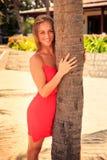 la ragazza bionda negli sguardi di rosso dalla palma guarda in avanti contro le piante Immagini Stock Libere da Diritti
