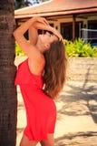 la ragazza bionda nel rosso si appoggia gli sguardi della palma verso l'alto contro la villa Immagine Stock