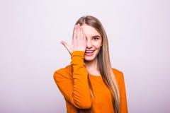 la ragazza bionda nella fine arancio una della maglietta osserva con la mano su bianco Immagini Stock