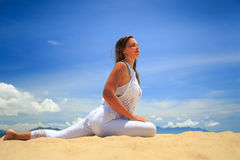 la ragazza bionda in pizzo in asana di yoga ha lasciato il tratto della gamba sulla spiaggia Immagine Stock