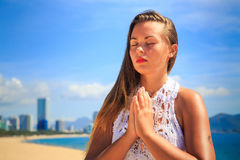 la ragazza bionda in pizzo si siede nel colpo di fulmine di asana di yoga sulla spiaggia Immagine Stock