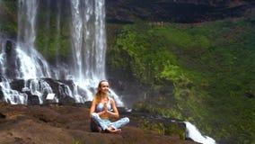 La ragazza bionda si siede nella posa di yoga di pranayama su roccia alla cascata video d archivio