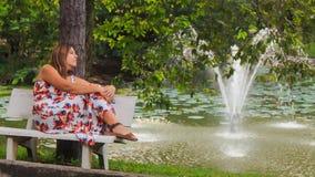 La ragazza bionda si siede sugli sguardi del banco alla fontana in parco stock footage