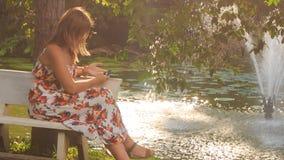La ragazza bionda si siede sul banco ai giochi della fontana con Iphone stock footage