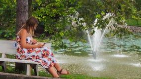 La ragazza bionda si siede sul banco ai tocchi Iphone della fontana in parco archivi video