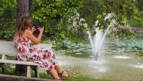 La ragazza bionda si siede sul banco alla fontana prende le foto con Iphone stock footage