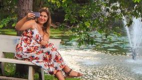 La ragazza bionda si siede sul banco fa Selfie dalla fontana in parco archivi video