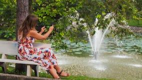 La ragazza bionda si siede sul banco prende la foto della fontana con Iphone video d archivio
