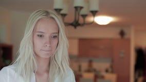 La ragazza bionda sta in appartamento, gira intorno e funziona verso la porta per aprirla archivi video