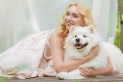 La ragazza bionda sta trovandosi all'aperto con un cane bianco in mani Immagine Stock