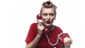 La ragazza bionda stupita con la bella acconciatura sta parlando sul suo vecchio telefono, movimento lento video d archivio