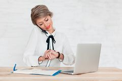La ragazza in blusa bianca si siede alla tavola con il computer portatile ed esamina l'orologio immagine stock