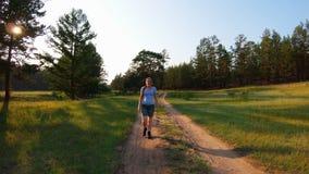 La ragazza in breve e vetri blu che camminano su una strada campestre al tramonto stock footage