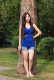 La ragazza in breve ha peso contro un albero nel parco Immagine Stock