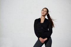 La ragazza in buona salute atletica si è vestita in abiti sportivi che posano all'aperto Fotografie Stock