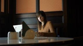 La ragazza in caffè parla sul telefono e beve il caffè video d archivio
